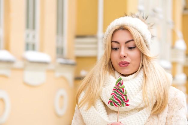 Emotionele blonde vrouw met lang haar met een warme gebreide muts, met heerlijke kerstsnoepjes