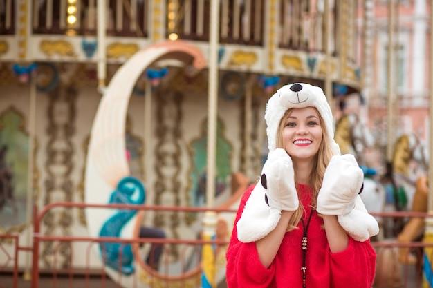 Emotionele blonde vrouw met rode gebreide trui en grappige hoed, poseren op de achtergrond van carrousel met verlichting