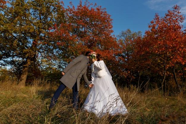 Emotionele bruid en bruidegom knuffelen en zoenen buitenshuis in rode herfst park. tedere gevoelens voor pasgetrouwden in het park. trouwdag . silhouet van bruidspaar op zonsondergang op de natuur