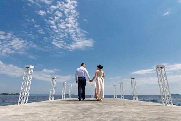 Emotionele bruid en bruidegom lopen op de brug in zonnige dag. trouwdag. man en vrouw kijken elkaar zacht aan en houden elkaar buitenshuis vast. romantisch moment op de datum