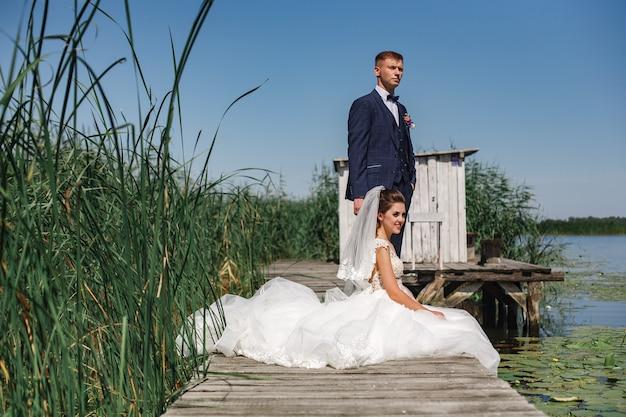 Emotionele bruidegom en bruid op houten brug in de buurt van de rivier in zonnige dag. portret van gelukkige jonggehuwden over de aard.