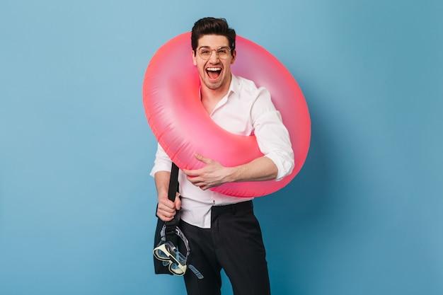 Emotionele brunette man in office outfit lacht. man in glazen poseren met roze rubberen ring en zwemmasker op blauwe ruimte.