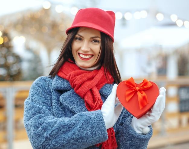 Emotionele brunette vrouw in winterjas met een geschenkdoos op kerstmarkt