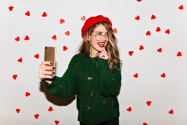 Emotionele culrly vrouw in baret met behulp van telefoon voor selfie op witte muur