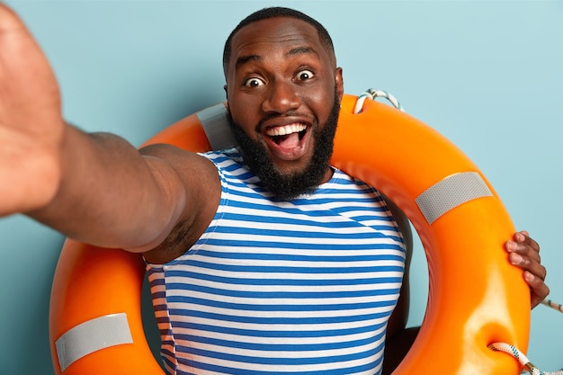 Emotionele dolgelukkig afro-amerikaanse redder in nood houdt arm gestrekt, poseert voor het maken van selfie, gebruikt levensreddende apparatuur, glimlacht breed