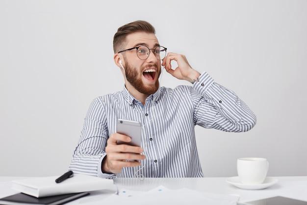 Emotionele dolgelukkig bebaarde man kijkt opgewonden opzij, luistert naar audiotrack met koptelefoon