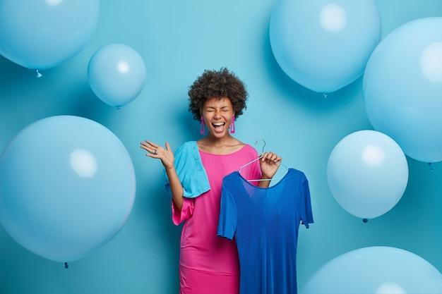 Emotionele dolgelukkige dame met een donkere huid, blij met de gelegenheid om haar favoriete outfit te dragen, poseert met een lange blauwe jurk aan een hanger, heeft een uitstekend humeur, geniet van feesten en vakantie-voorbereiding. mode