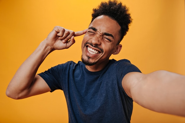 Emotionele donkere man in t-shirt maakt selfie op oranje muur