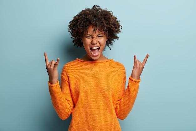 Emotionele donkere vrouw maakt rock n roll-gebaar, geniet van coole muziek op feestje, fronst gezicht, opent mond, toont handgebaar, gekleed in oranje trui, modellen over blauwe muur