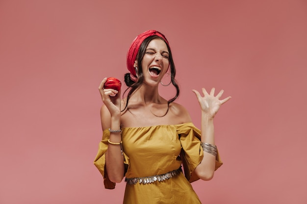 Emotionele donkerharige dame met stijlvolle accessoires en lichte zomerjurk met rode appel en schreeuwend op roze muur