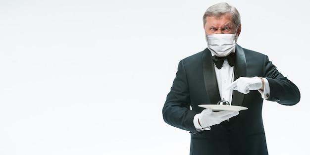 Emotionele elegantie senior man ober in beschermend gezichtsmasker op witte achtergrond