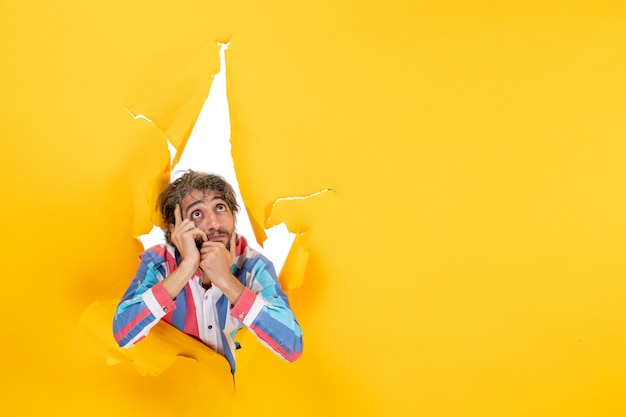 Emotionele en dromerige jonge man in gescheurde gele papieren gatenachtergrond