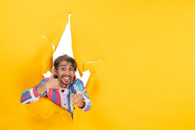 Emotionele en glimlachende jonge man die me een gebaar maakt op een gescheurde gele papieren gatenachtergrond