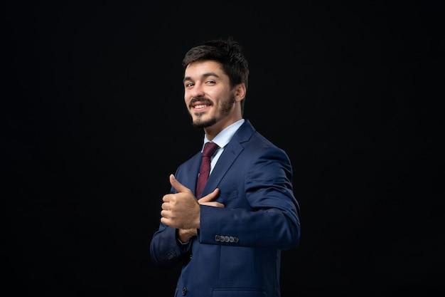Emotionele en jonge bebaarde man die een goed gebaar maakt op een geïsoleerde donkere muur