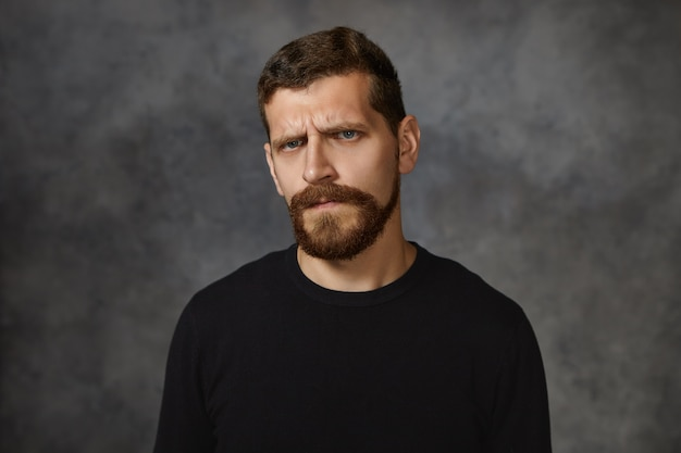 Emotionele europese jonge man met wazige baard, fronsend, ontevreden gelaatsuitdrukking, boos zijn op zijn kinderen vanwege slecht gedrag, ergernis en irritatie tonen