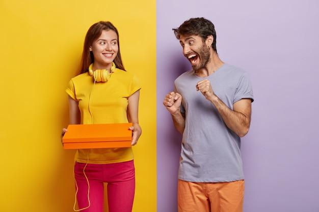 Emotionele europese man balde vuisten en juicht toe terwijl hij naar het pakket in de handen van de vrouw kijkt, kan niet wachten en wil zijn cadeau uitpakken, draagt een paars casual t-shirt.