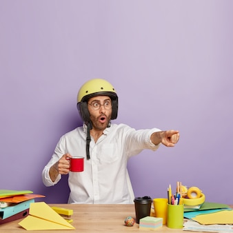 Emotionele europese mannelijke werknemer wijst in de verte, expressie heeft bang, draagt beschermende helm, mok koffie houdt, werkt op het bureaublad in zijn kast