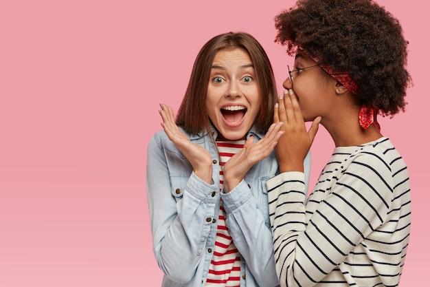 Emotionele europese vrouw vouwt de handen en roept luid als ze geruchten hoort van beste vriend. afro-amerikaanse vrouw fluistert geheim in het oor van haar metgezellen