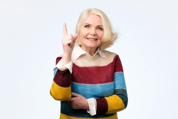 Emotionele expressieve oude vrouw met wijsvinger omhoog