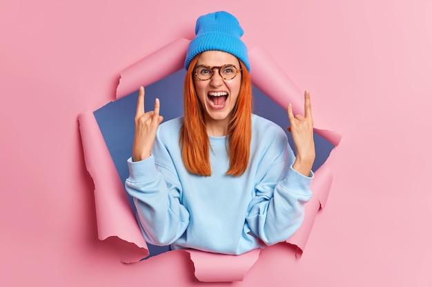 Emotionele gekke roodharige jonge vrouw maakt stenen bord gebaren vinger hoorns roept vreugdevol draagt blauwe hoed en sweatshirt breekt door papier gat