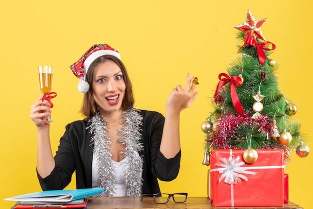 Emotionele gelukkig tevreden charmante dame in pak met kerstman hoed en nieuwjaarsversieringen wijn verhogen in het kantoor op geel geïsoleerd