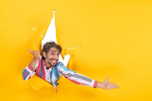 Emotionele gelukkige en lachende jonge man in gescheurde gele papieren gat achtergrond