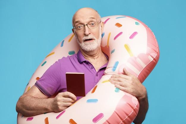 Emotionele geschokte oudere man met grijze baard die in paniek raakt omdat hij bijna te laat is voor de bus die vakantie aan zee gaat doorbrengen, met opblaasbare cirkel en internationaal paspoort om naar het buitenland te reizen