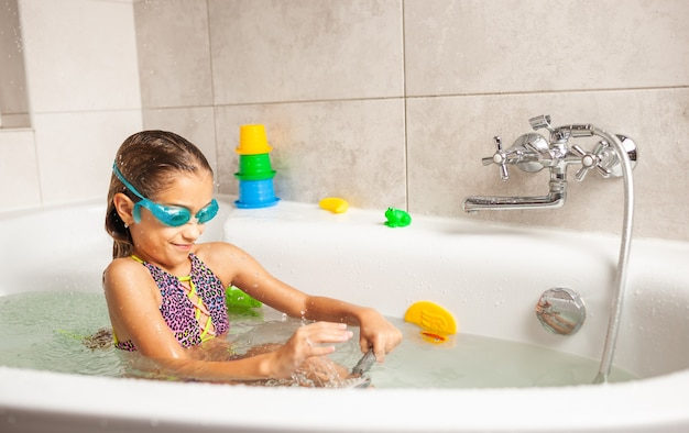 Emotionele grappig kaukasisch meisje speelt vreugdevol met water tijdens het baden in de badkamer
