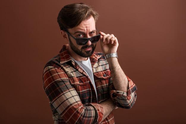 Emotionele hipster knappe stijlvolle bebaarde man met grappige gezichtsuitdrukking op bruin
