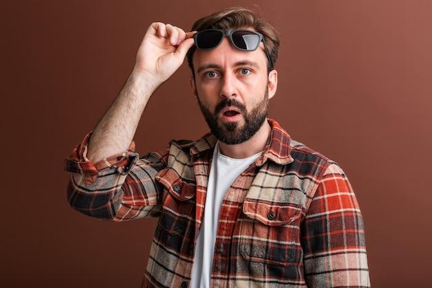 Emotionele hipster knappe stijlvolle bebaarde man op bruin