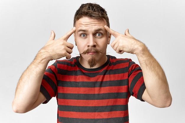 Emotionele hipster-man met stuursnor die verontwaardiging uitdrukt, naar de camera staart en zijn vingers naar zijn slapen houdt alsof hij zegt: gebruik je hersenen! stijlvolle bebaarde man die zich gestrest voelt