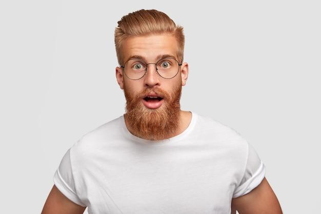 Emotionele hipster met een verbijsterde uitdrukking, vraagt zich af van het laatste nieuws, heeft een dikke rode baard en snor