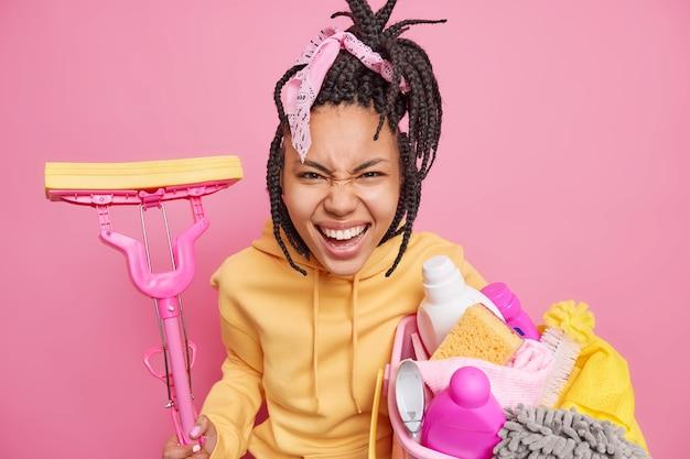 Emotionele huisvrouw met donkere huidskleur heeft dreadlocks roept uit en grijnsde gezichtshoudingen met schoonmaakgereedschap