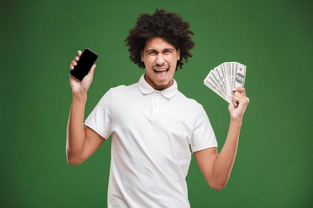 Emotionele jonge afrikaanse krullende man met weergave van het geld van de mobiele telefoonholding.