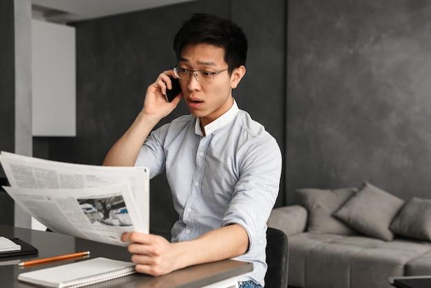 Emotionele jonge aziatische man praten via de telefoon