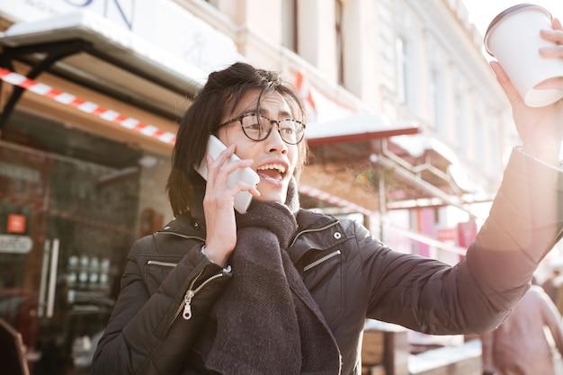 Emotionele jonge aziatische mens die koffie drinkt en telefonisch spreekt.