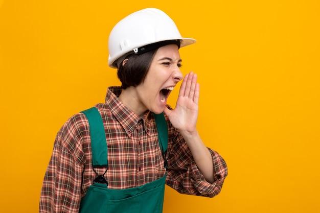 Emotionele jonge bouwvrouw in bouwuniform en veiligheidshelm die schreeuwt of iemand belt die de hand in de buurt van de mond houdt die op oranje staat