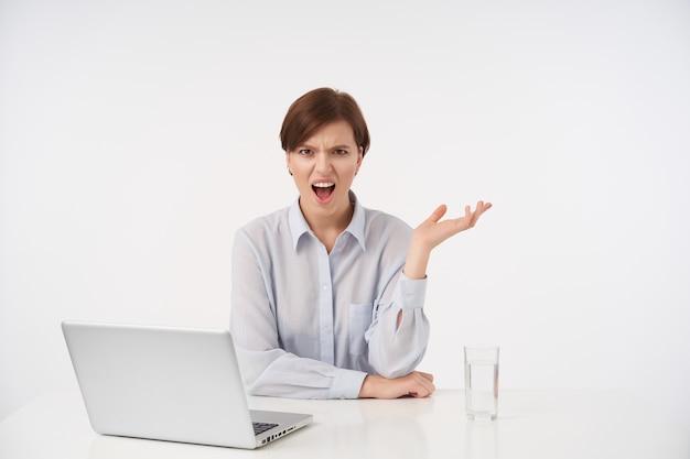 Emotionele jonge bruinogige brunette vrouw met casual kapsel boos kijken met brede mond geopend en haar handpalm verhogen terwijl poseren op wit