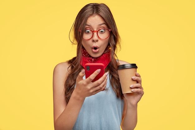 Emotionele jonge brunette met bril poseren tegen de gele muur
