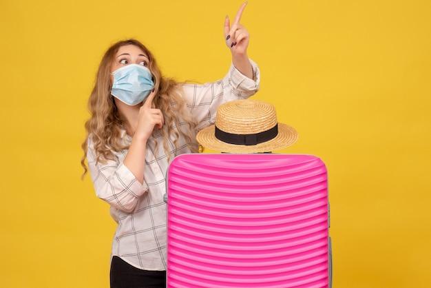 Emotionele jonge dame die masker draagt dat kaartje toont en zich achter haar roze zak bevindt die omhoog wijst