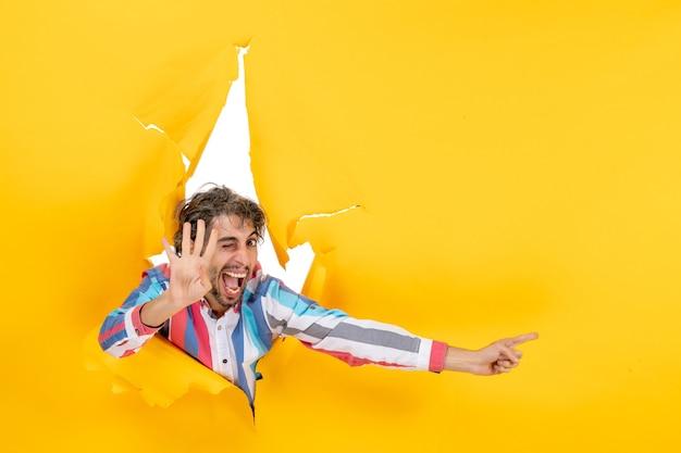 Emotionele jonge man die iets aan de linkerkant wijst en vier laat zien in een gescheurde gele papieren gatenachtergrond