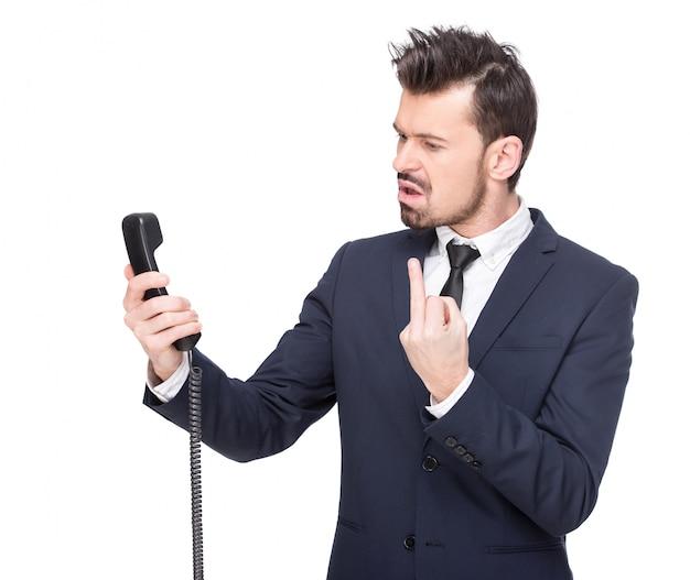 Emotionele jonge man schreeuwt aan de telefoon.