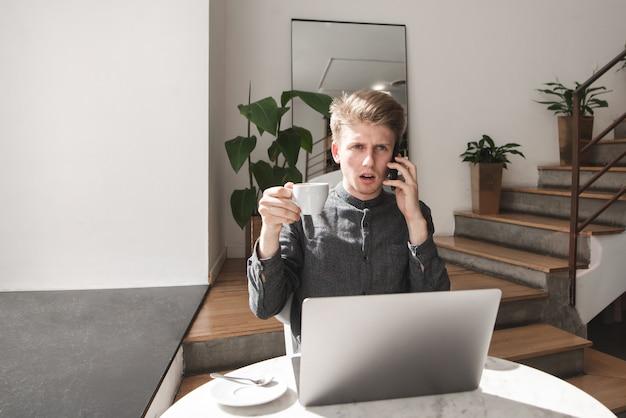 Emotionele jonge man zit aan de tafel in een licht café met een laptop en een kopje koffie in de hand