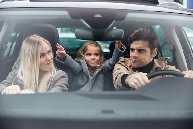 Emotionele jonge man zit in auto met zijn grappige vrouw