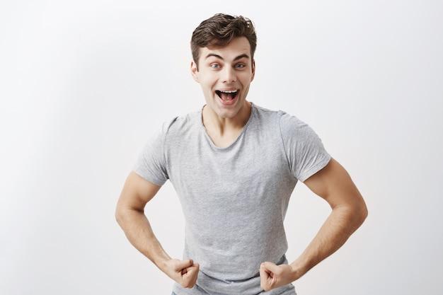Emotionele jonge mannelijke atleet met gespierd lichaam, breed glimlachend, die laat zien hoe sterk hij is, pronkt met zichzelf. positieve man toont zijn spieren en kracht, poseren.