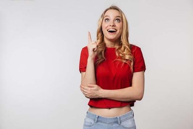 Emotionele jonge mooie mooie vrouw poseren geïsoleerd over witte muur heb een idee wijzend