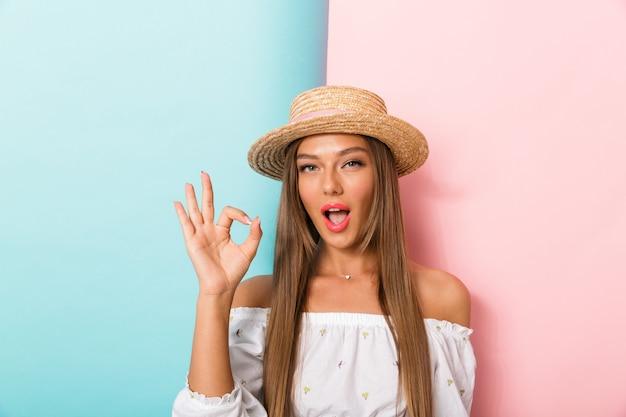 Emotionele jonge mooie vrouw poseren geïsoleerd dragen hoed maken goed gebaar.