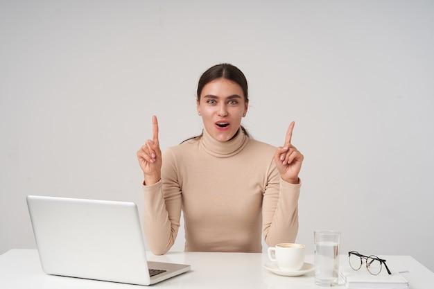 Emotionele jonge vrij donkerharige vrouw met paardenstaart kapsel handen verhogen als ze idee heeft en op zoek met opgewonden gezicht, poseren over witte muur