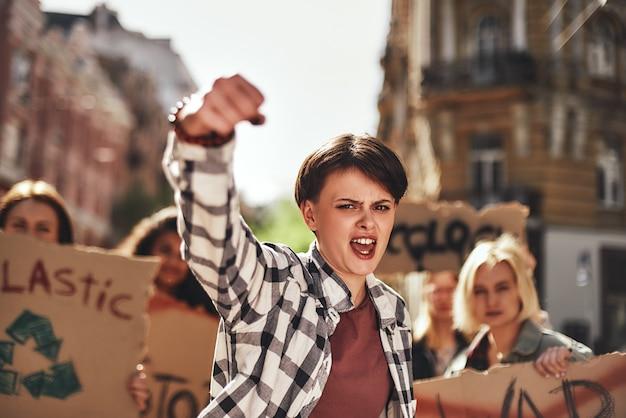 Emotionele jonge vrouw die een slogan schreeuwt en een groep demonstranten op de weg leidt
