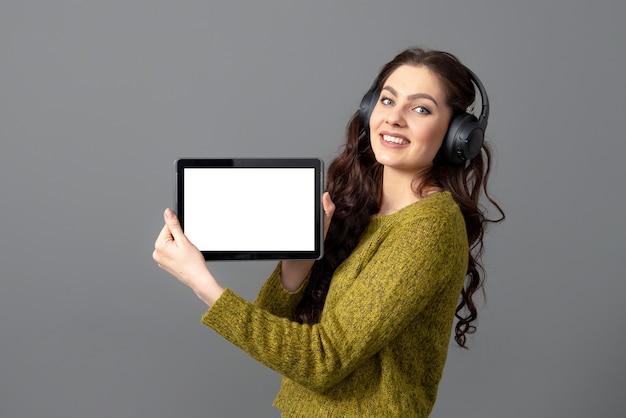 Emotionele jonge vrouw die tabletcomputer met leeg aanrakingsscherm met exemplaarruimte toont, die op grijze muur wordt geïsoleerd